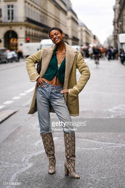 Model wears earrings, a necklace, a green knit crop top with a plunging neckline, ripped blue jeans, a beige shearling jacket, light brown and black...