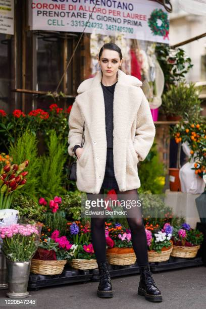 Model wears earrings, a white fluffy coat, a black top, a short skirt, tights, a bag, black leather Dr Martens shoes, outside Koche x Pucci, during...