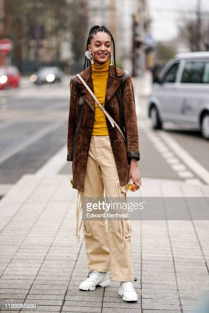 A model wears earrings a yellow turtleneck a brown suede coat beige pants white Dior sneakers outside Nina Ricci during Paris Fashion Week Womenswear...
