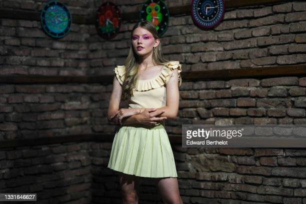 Model wears gold and silver earrings, a gold chain pendant necklace, a pale yellow ribbed ruffled V-neck sleeveless t-shirt, a pale green pleated /...