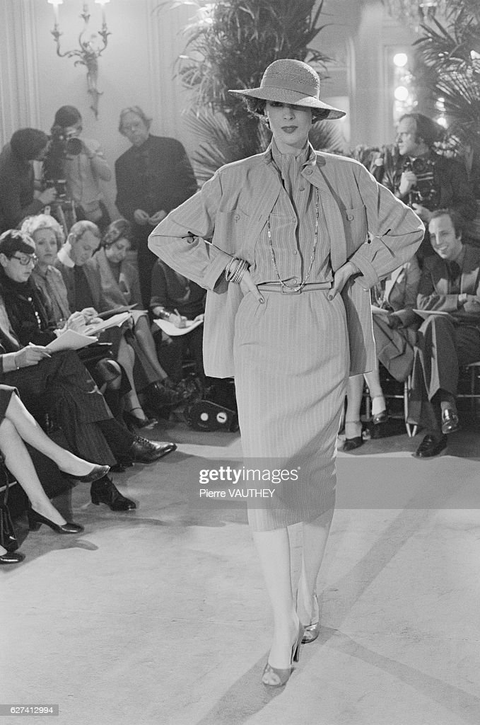 A model wears haute couture women's fashions by designer Marc Bohan from French fashion house Christian Dior during a 1976 Spring-Summer fashion show in Paris. She wears a belted, pinstriped dress, jacket and brimmed hat.