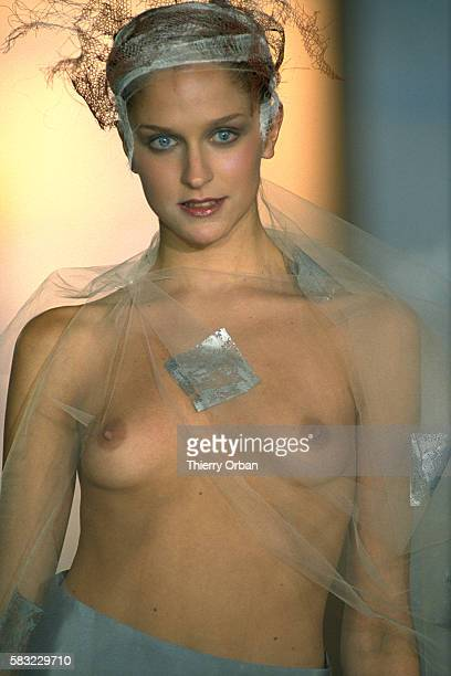A model wears haute couture women's fashions from French designer Christophe Rouxel in a 1999 springsummer fashion show She appears barebreasted with...