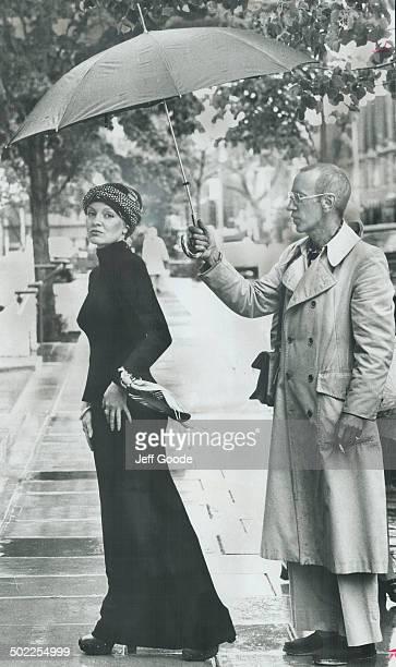 Model wears new Yorkdesigned dress of black knit Toronto designer John Burkholder gallantly holds the umbrella as spring rain falls