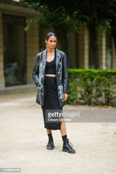 Model wears silver chain necklaces, silver snake pendant rings, a black V-neck ribbed t-shirt, a black long blazer jacket with white embroidered...