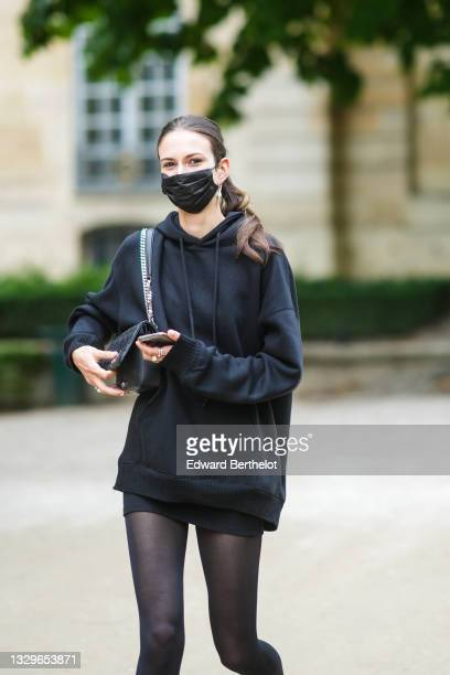 Model wears silver earrings, a black oversized hoodie sweaters, black tights, a black skirt, a black shiny leather shoulder bag, silver rings,...