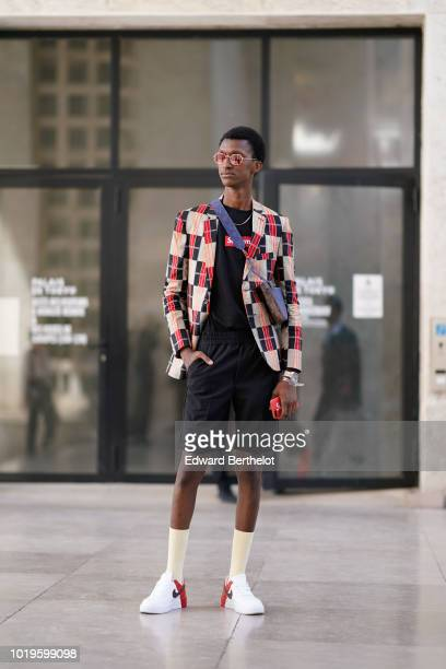 A model wears sunglasses a black and red checked pattern blazer jacket a black tshirt from Supreme black shorts socks Nike sneakers outside Juun J...