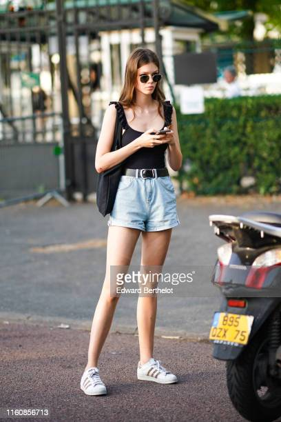 A model wears sunglasses a black top a black tote bag a black belt light blue denim shorts white Adidas sneakers outside Miu Miu Club 2020 on June 29...