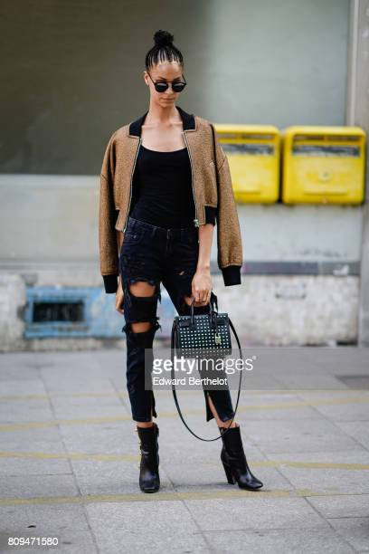 A model wears sunglasses a bomber jacket a black top black ripped jeans a studded bag black boots outside the Jean Paul Gaultier show during Paris...