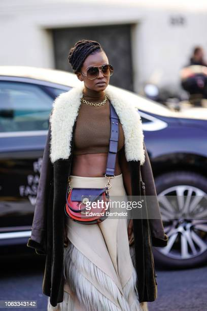 A model wears sunglasses a brown cropped top a red Chloe bag a white faux fur skirt a brown aviator jacket with white wool inner lining outside Chloe...