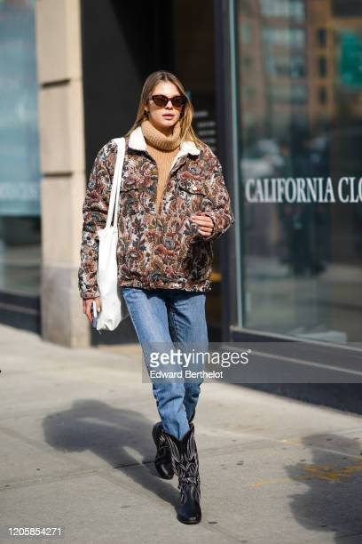 Model wears sunglasses, a brown wool pullover, a floral print multicolor jacket, a belt, blue denim jeans, leather cowboy boots, a white tote bag,...