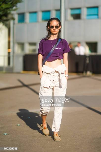 A model wears sunglasses a Chanel necklace a purple tshirt with the inscription Samizdat a white denim jumpsuit beige shoes outside Acne during Paris...