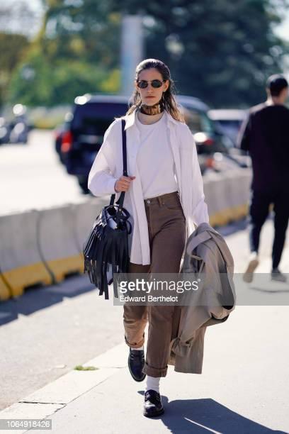 A model wears sunglasses a choker a white tshirt a white oversize shirt brown pants white socks black shoes a bag with fringes outside Margiela...