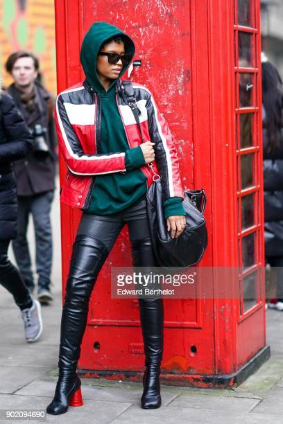 A model wears sunglasses a green hoodie sweater a blue white and red striped leather jacket black leather pants black thigh high leather boots with...