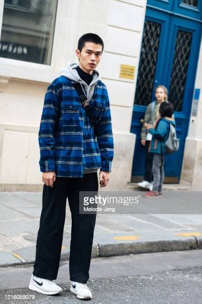 Model Wen Qiming wears a blue plaid shirt, cross body bag, black pants, and white Nike sneakers after J.W. Anderson on January 15, 2020 in Paris,...