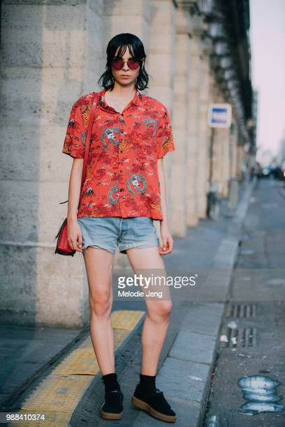 Model Willy Morsch in an orange print top and jean shorts outside the Miu Miu Cruise 2019 show on June 30 2018 in Paris France