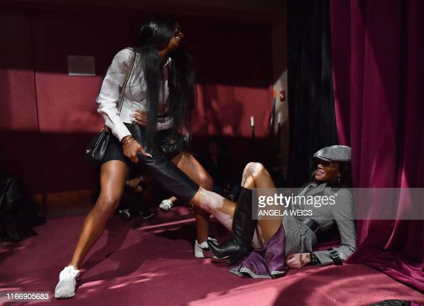 TOPSHOT Model Winnie Harlow is helped out of her boots at the Tommy Hilfiger TommyNow fall runway show at the Apollo Theater on September 8 2019 in...