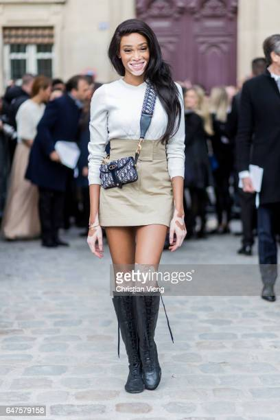 Model Winnie Harlow wearing white knit mini skirt boots Dior bag outside Dior on March 3 2017 in Paris France