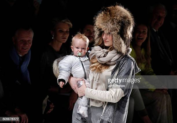 A model with a baby walks the runway at the Sportalm show during the MercedesBenz Fashion Week Berlin Autumn/Winter 2016 at Brandenburg Gate on...