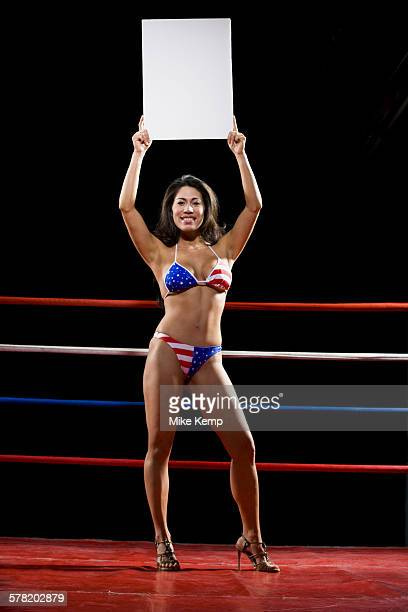 Model with a blank sign in a boxing ring