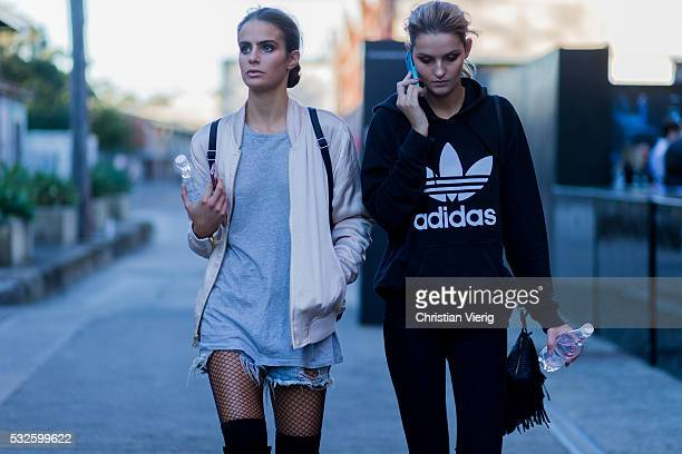 A model with a creme bomber jacket ripped denim shorts grey tshirt and black fishnet tights and a model with a black Adidas hoody and denim jeans at...