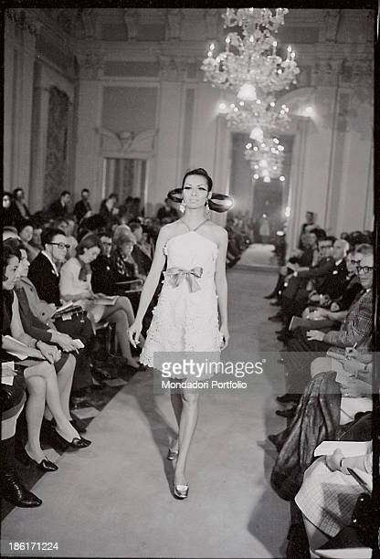 A model with a fanciful hairstyle wearing a dress with a ribbon catwalking at Palazzo Pitti Florence 1960s
