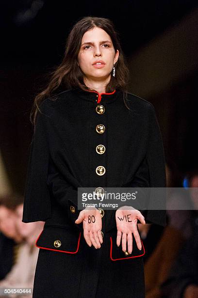 A model with 'Bowie' written on her hands walks the runway at the Burberry show during The London Collections Men AW16 at Kensington Gardens on...