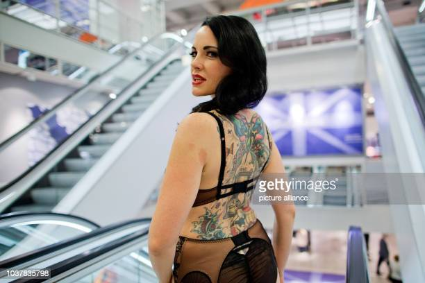 A model with tattoos on her back and wearing lingerie from a collection designed by Burlesque model Dita von Teese stands in front of escalators of a...
