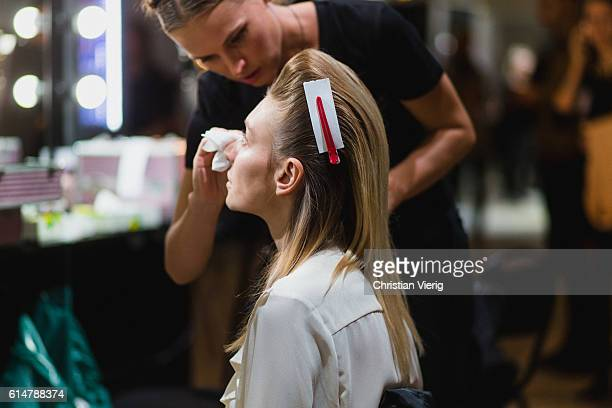 A model with wet backcombed hair getting her make up removed is seen backstage ahead of the Saint Tokyo show during the MercedesBenz Fashion Week...