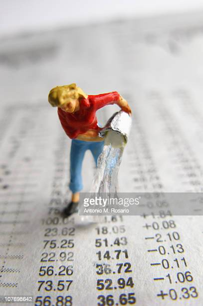 Model woman pouring water on financial figures