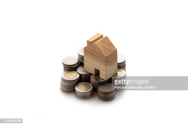 model wood house placed on a stack of coins isolated on white background, saving and invest concept - expense stock pictures, royalty-free photos & images