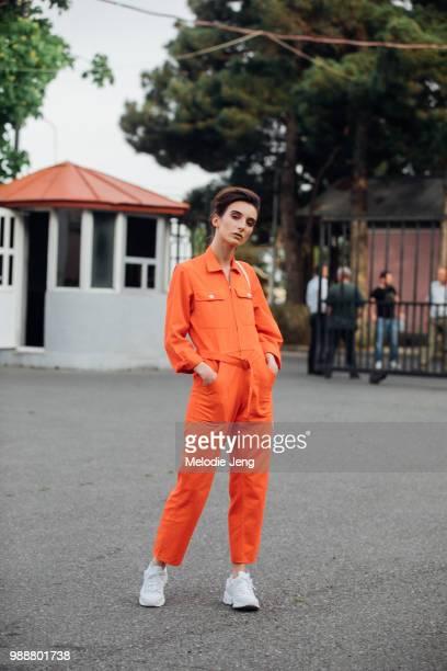 Model Xosilita Xose Xositashvili wears an orange jumpsuit and white sneakers during MercedesBenz Fashion Week Tbilisi Fall/Winter 2018 on May 7 2018...