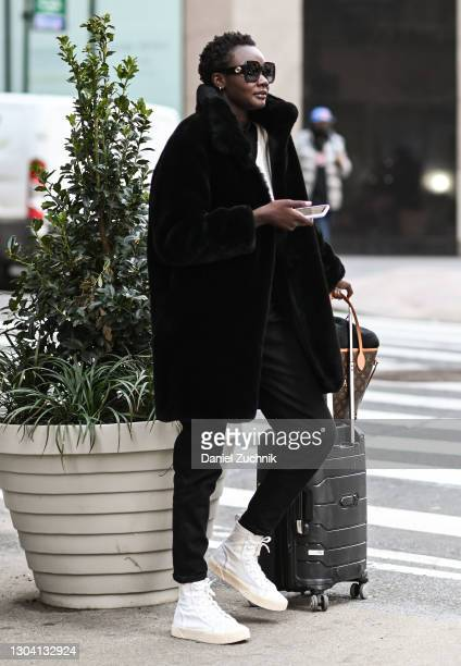 Model Ya Jagne is seen wearing a black coat, black pants and white sneakers with sunglasses outside the Christian Siriano show during New York...