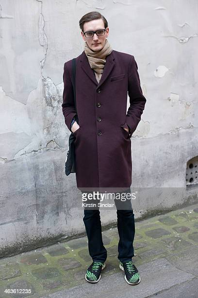 Model Yannick Abrath wears a Burberry coat Emporio Armani glasses Uniqlo jeans Nike trainers and a Raf Simons scarf day 4 of Paris Mens Fashion Week...