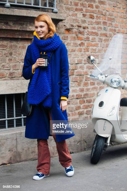 Model Yeva Podurian holds a thermos hot drink and wears a blue coat with an oversized blue knit scarf maroon pants and blue sneakers during Milan...