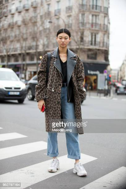 Model Yoon Young Bae wears a brown animal print jacket blue jeans and white chunky Disruptor II Fila sneakers on January 24 2018 in Paris France