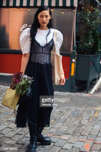 Model Yoonmi Sun wears a black sleeveless lace dress over a white shirt with exaggerated shoulders, black boots, a white Tory Sport tote bag, and...