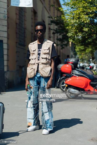 Model Zakarie Ali wears black sunglasses, a tan vest with pockets, and blue multi patch & quilt jeans after the Fendi show during the Milan Men's...
