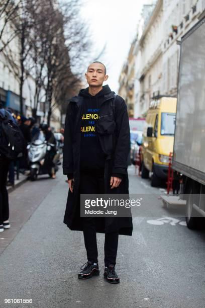 Model Zhang Wenhui wears all black a parka Balenciaga hoodie pants and Nike Air Max sneakers during Paris Fashion Week Menswear Fall/Winter 2018 on...
