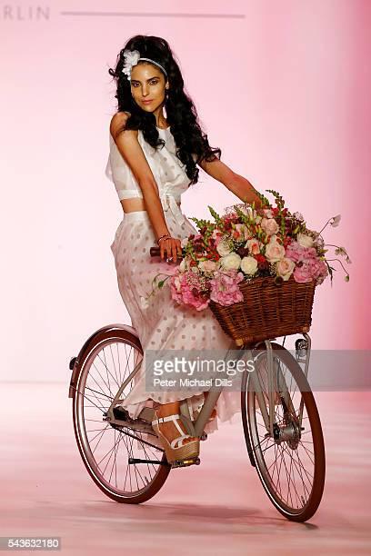 Model Zoe Helali rides a bike on the runway at the Guido Maria Kretschmer show during the MercedesBenz Fashion Week Berlin Spring/Summer 2017 at...