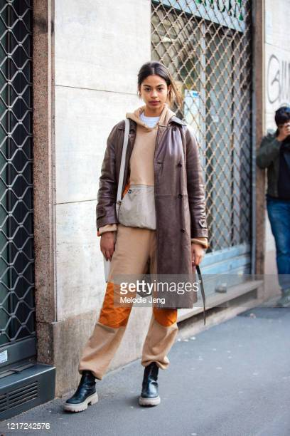 Model Zoe Thaets wears a brown leather jacket, matching light brown Stussy hoodie and sweatpants, and black boots after the Dolce & Gabbana show...