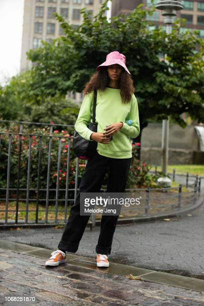 Model Zoe Thaets wears a pink rain hat green sweater black pants and pink orange Converse sneakers after the Zimmermann show during New York Fashion...