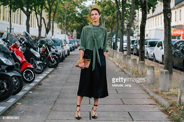 Model/Actress Aymeline Valade a wears Loewe outfit including a green top with a front tie and black culottes, after the Loewe show at Maison de...