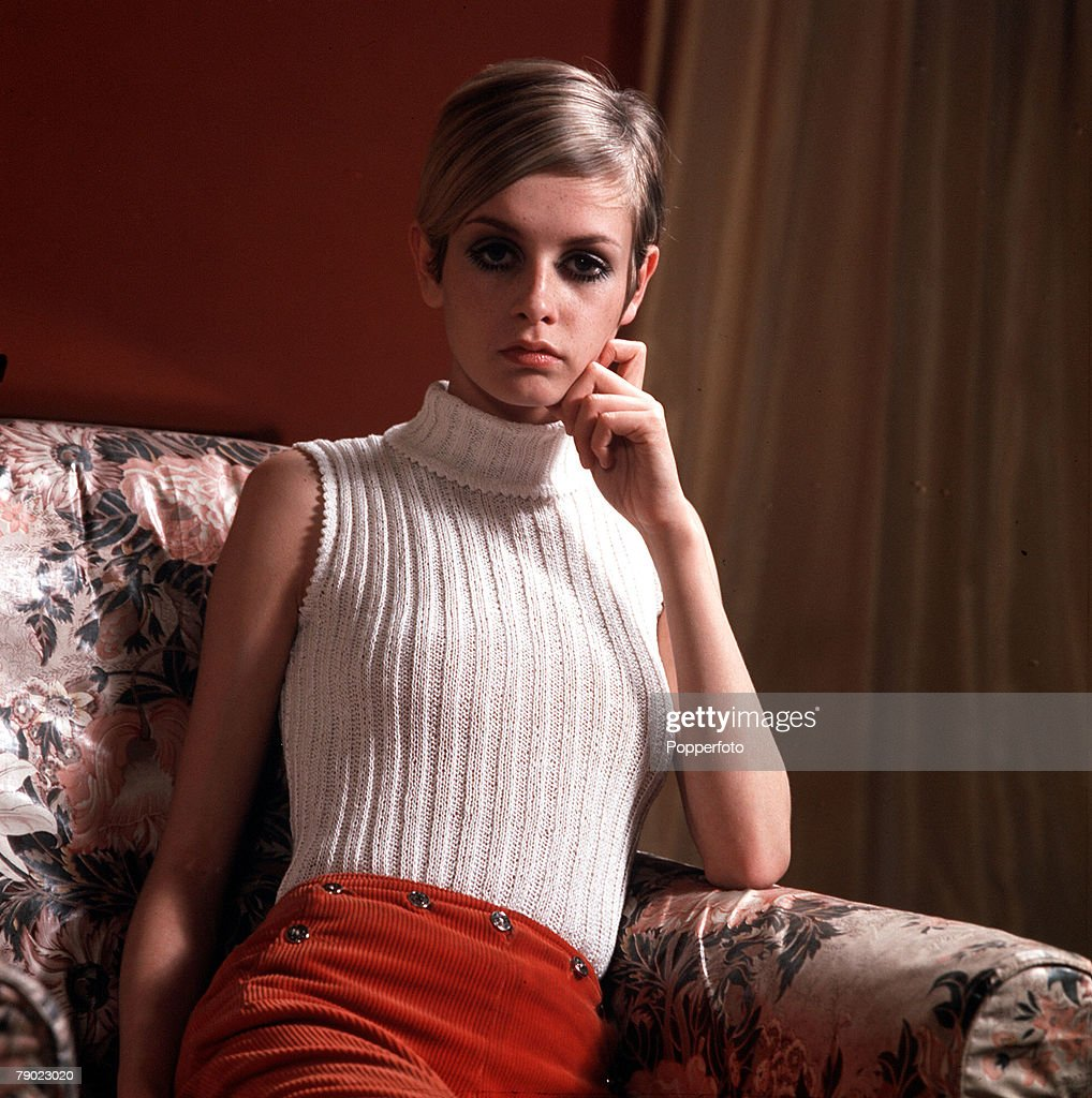 1967. Modelling. A picture of British model Twiggy wearing a fashionable sleeveless, beige polo neck jumper and red trousers, as she poses on a settee. : News Photo