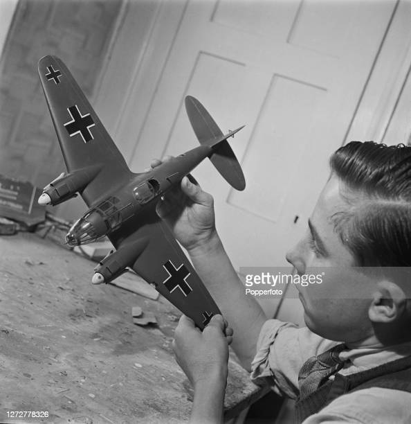 A modelmaker completes a final visual check of a model of a German Luftwaffe Heinkel He 111 K bomber aircraft at the Woodason Aircraft Models company...