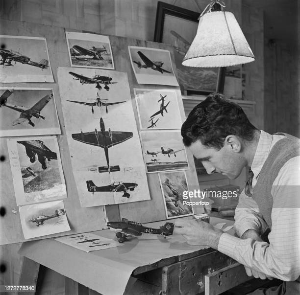 A modelmaker completes the finishing touches to a model of a German Luftwaffe Junkers Ju 87 B dive bomber ground attack aircraft at the Woodason...