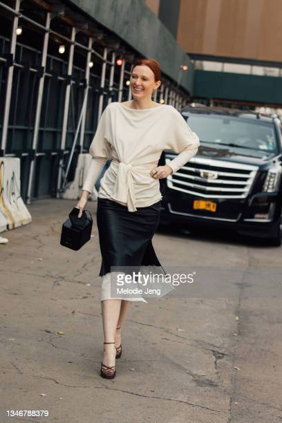 Model/Musician Karen Elson wears a white front-tie cashmere sweater, black skirt, black square purse, and brown heels at the Khaite show on September...