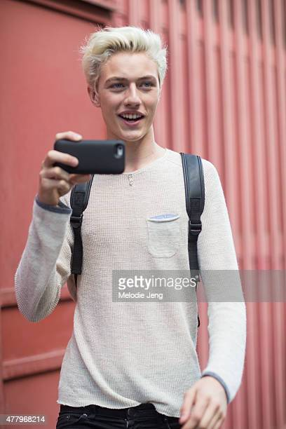 Model/Musician Lucky Blue Smith exits the Salvatore Ferragamo show and shoots a video of the photographers on June 21 2015 in Milan Italy