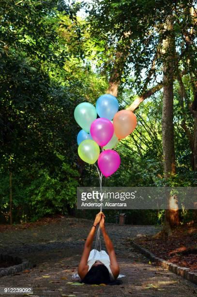 Modelo segurando Balões coloridos em composição com natureza. Joao Pessoa, Paraíba, Brasil. Fotografia