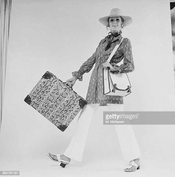 Models a pair of white trousers and hat with a suitcase in a reptile print, UK, 29th June 1970.