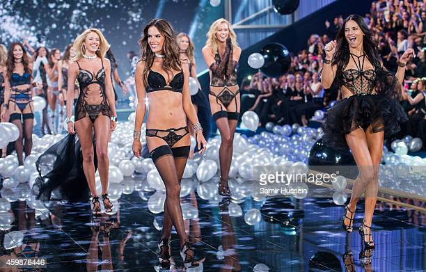 Models Adriana Lima and Alessandra Ambrosio lead out the models as they walk the runway at the annual Victoria's Secret fashion show at Earls Court...
